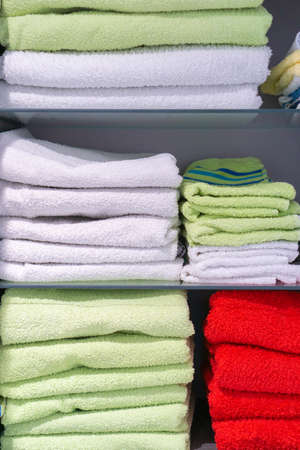 White green and red towels neatly stacked in a cupboard Zdjęcie Seryjne