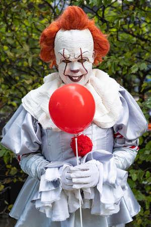Przerażający klaun z czerwonym balonem