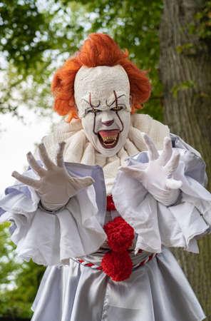 Dangerous horror clown reaches for a victim with his hands 版權商用圖片