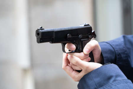 Woman holds a pistol in her hand Stock Photo