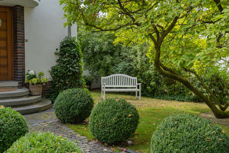white wooden bench in a front yard Stockfoto
