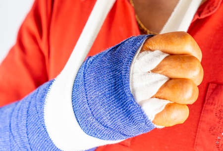Woman in red sweater with freshly operated hand with blue bandage and disinfectant orange fingers
