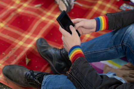 Man sits on a red checkered blanket and taps his cellphone Reklamní fotografie