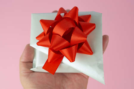 Woman holds a white wrapped gift with red bow in her hand, pink background