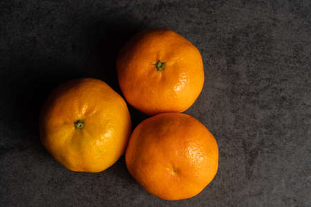 Three fresh tangerines on black background, view from above
