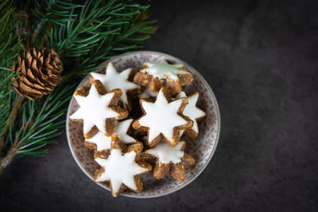 A cup with christmas biscuits and fir branch on a black table and copy space, top view Stock fotó