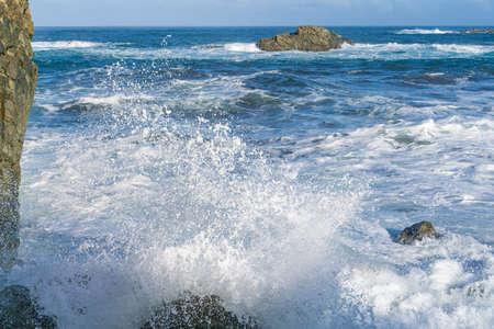 Der raue Atlantik in der Nähe von Teneriffa, Spanien, starke Wellen brechen an den Felsen im Wasser