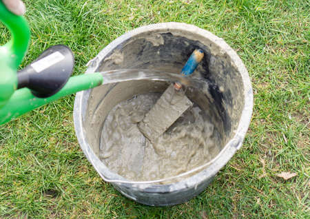 With a watering can, water is poured into a mortar bucket with a trowel to clean bucket and trowel