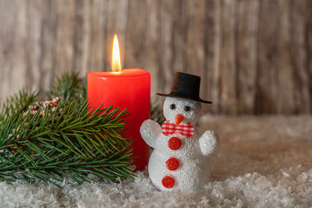 Burning red candle with a little snowman in the snow, copy space