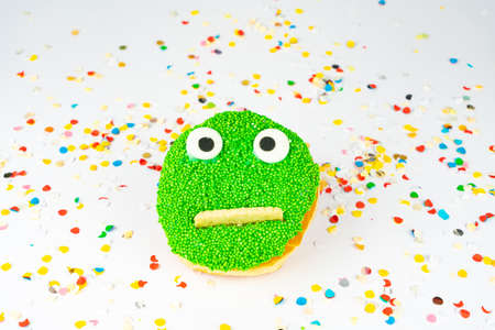 Funny green face cake with confetti background 免版税图像