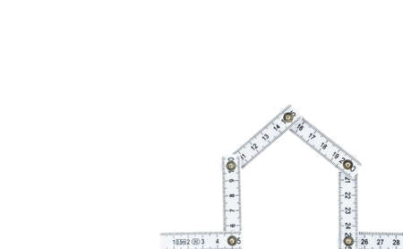 Folding rule in the shape of a house, white background and copy space Standard-Bild