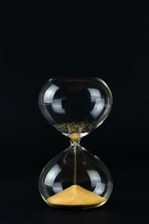 Hourglass with golden sand and black background, copy space