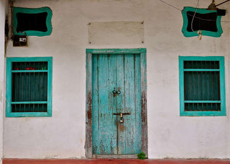 Old timber wooden house with turquoise windows and doors. Typical of Chinese clan houses. Stok Fotoğraf