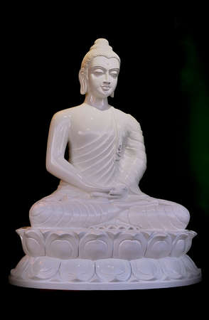 White alabaster statue of buddha sitting in the lotus postion. Reklamní fotografie