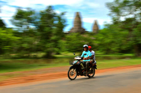 Motorcyclist speeding down a rurul road with a blurred Khmer temple in the background.