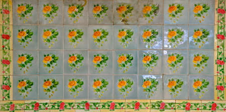 A mosaic of blue tiles decorated with yellow flowers. These are typical of the tiles found on the facade of traditional Chinese Peranakan shop houses.