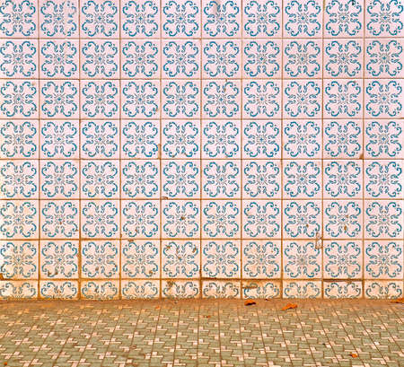 Peranakan tile mosaic as typically found on traditional Chinese shop houses, with a blue floral geometric design on a white background with green floor tiles in the foreground.