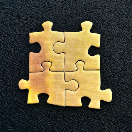 Four yellow jigsaw pieces isolated on a textured black background.