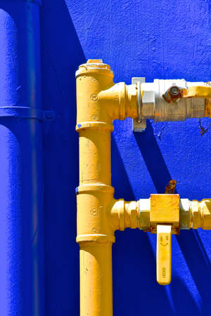Heavy duty industrial yellow, metal water pipes and taps, isolated against a dark blue background.