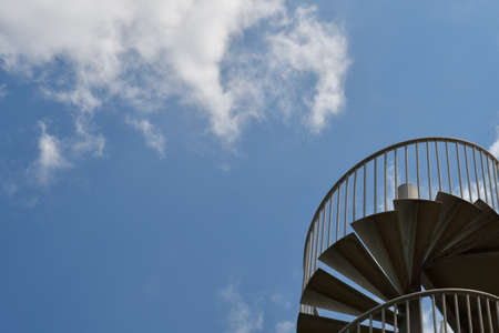 An abstract blue sky background with white clouds and a metal spiral staircase in the corner. 写真素材
