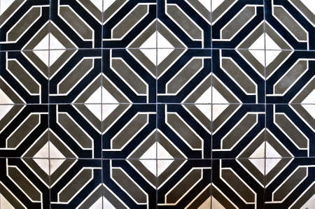 Peranakan tile mosaic as typically found on traditional Chinese shop houses, with a geometric, symmetrical repeating pattern of grey, white and navy blue shapes.