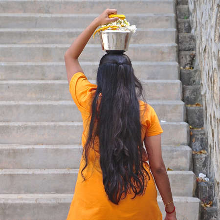 Rear view of young Hindu girl with long hair, carrying a stainless steel urn of milk during the festival of Thaipusam.