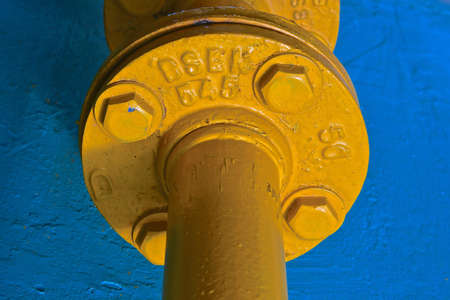 A close up view of a large yellow industrial pipe against a blue stone background.