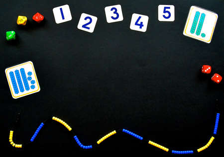 Maths concept flatlay on a black background with copyspace, focusing on number, addition, sibtraction and counting with beaded number lines, place value dice and problem task cards.