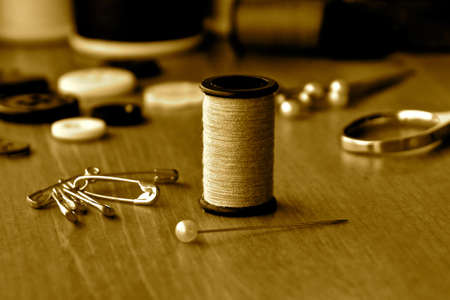 A close up view of a cotton reel amongst an array of sewing accessories in sepia tones.