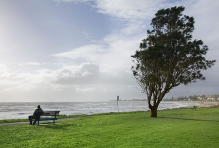 man sitting alone on a park bench photo