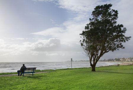 bench alone: man sitting alone on a park bench