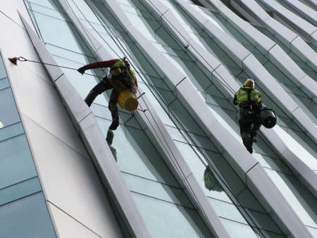 iron curtain: Construction abseilers fix curtain wall of building Editorial