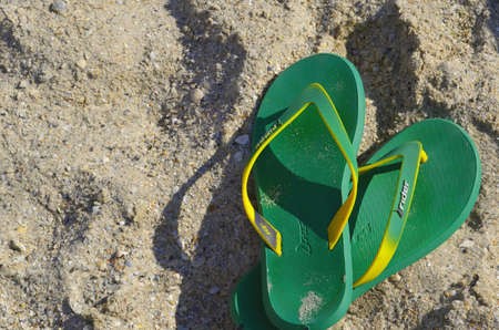 Summer slippers on a sandy beach. Green slippers.