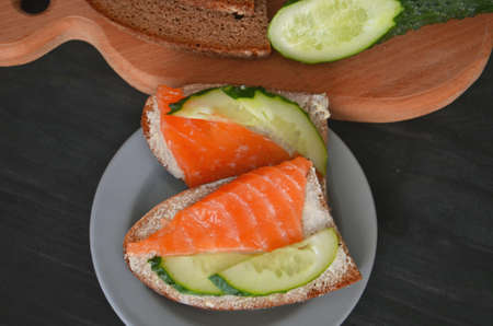 Healthy breakfast. sandwich with salmon and cucumber, brown bread and butter on a wooden background.