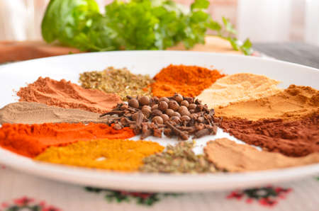 Set of oriental spices in a plate on a wooden table. Parsley, basil, cilantro. View from above.