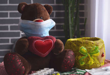 Toy teddy bear in a medical mask on a gray background. Pills for treating a pet.