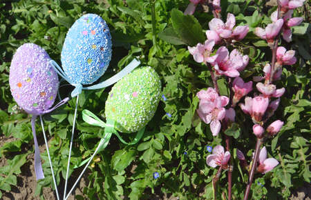 Easter decorative eggs in the grass with flowers and a basket. Easter decoration.