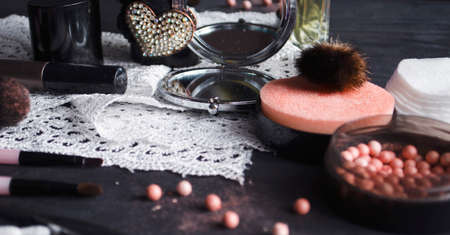 Cosmetics on a dark background, close-up. Face care, make-up. Items for applying makeup. The world of a woman.