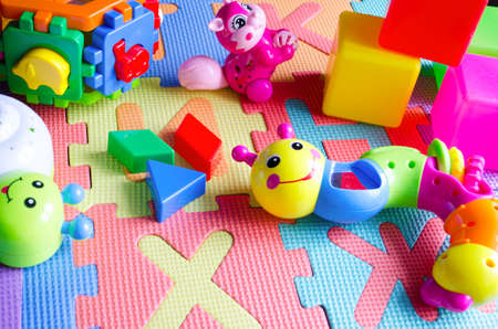 Educational children's bright toys on the table. Puzzles, rattles, cubes and mechanical squirrel. Toys zero and older. Child's world.