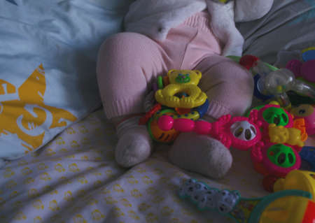 Small legs next to many toys on a light background. Legs in socks and pants. Rattles at the feet of the child. Close-up.