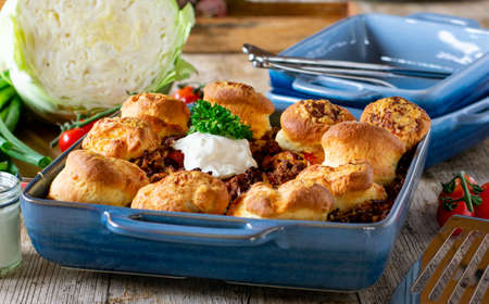 Irish cobbler with scones. Dish from Ireland with minced meat, cabbage, tomatoes, onion oven baked with bread and topped with cheese and sour cream in a baking dish