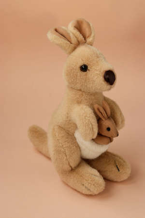 Soft toy mom kangaroo with a baby is located on a peach background, vertical