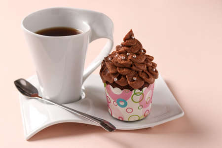 Homemade chocolate cream cupcake and a cup of coffee arranged on a pink background