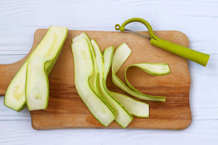 Zucchini, cut with ribbons using vegetable cutters. Located on a wooden board on a white background, top view
