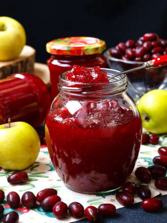 Homemade jam of dogwoods and apples is located in the jars on the table, one jar is open, Preparation of jam for the winter