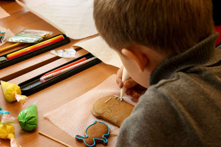 Lesson of creativity in elementary school, children learn to decorate Easter gingerbread with glaze