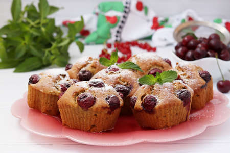 Cupcakes with cherries are located on a plate on a white background 写真素材
