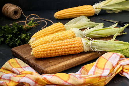 Fresh, peeled corn is located on a wooden board against a dark background, next to it is a bunch of parsley