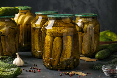 Different pickled cucumbers with zucchini, onions, garlic and grape leaves in jars on a dark background, horizontal photo
