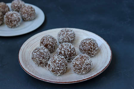 Curd balls with coconut shavings and chocolate chip cookies re located on a dark background, horizontal photo 免版税图像